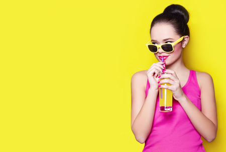 Beautiful young girl in studio on a yellow background and yellow sunglasses drinking yellow juice through a straw. She smiles and looks. The hairstyle is raised to the top. Advertising, beauty.