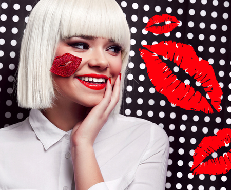 Beautiful girl in a white wig On a black and white background in polka dots. A young girl in the studio with a kiss on her cheek in a white wig and a white shirt smiles. Red lipstick, pop art.