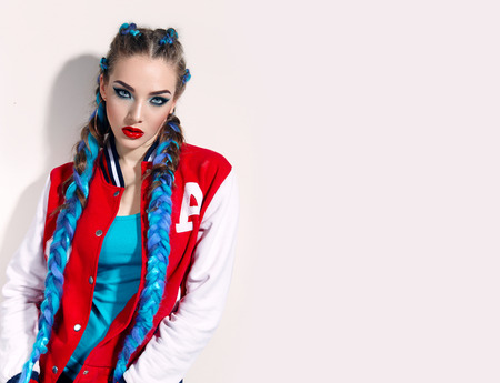 Beautiful young girl with long bright braids. Blue hair, weaving, Bright makeup, red jacket. Cosmetics. Photoshoot on a white background. Stock Photo