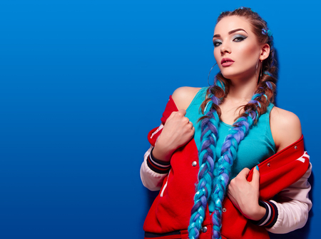 Beautiful young girl with long bright braids. Blue hair, weaving, Bright makeup, red jacket. Cosmetics. Photoshoot on a blue background.
