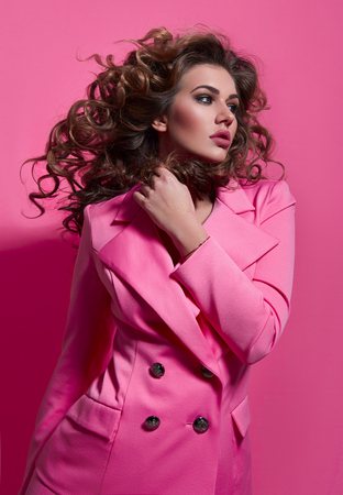 Beautiful fashionable girl haired with long curly hair in a pink jacket. The girl in the studio on a pink background.