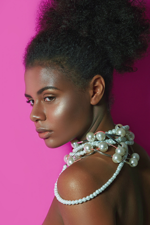 A beautiful African-American, dark-haired young girl stands on a pink background in the studio. Hairstyle Afro. Black curly hair is gathered in the tail. Necklace of pearls on the neck.Cosmetics