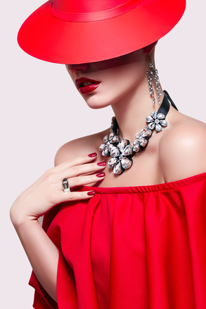 Beautiful young girl in a red dress and a red hat on a white background in the studio. Luxury jewelry, necklace and ring, bright makeup, red lips, manicure. Bohemia, glamor, luxury, beauty, fashion.