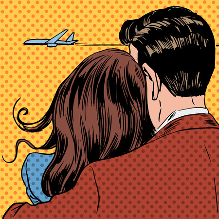 Loving couple looking at a plane taking off in the sky. A man and a woman hug and stand back