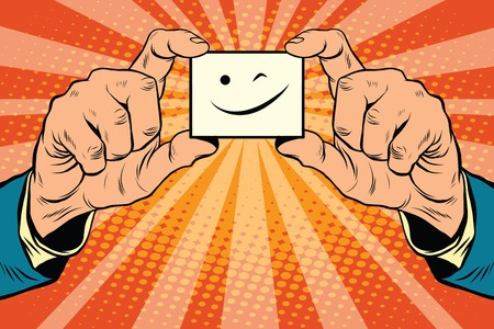 wink Smiley face in hands, pop art retro vector illustration