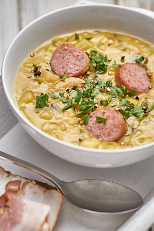 Traditional Dutch pea soup with smoked sausage and rye bread with bacon. Stock Photo