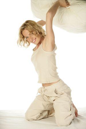 arrodillarse: Mujer que lucha de almohadas en la cama
