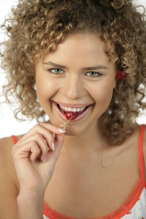 Young woman eating cherry photo