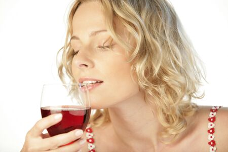 Young attractive woman drinking red wine on white background photo