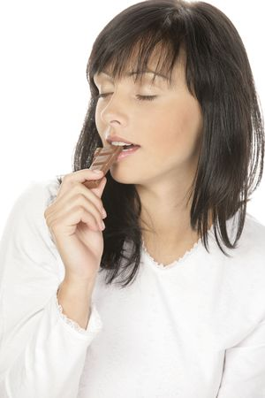 Young attractive beautiful woman eating chocolate on white background photo