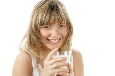 Laughing young woman holding glass of milk isolated on white background photo