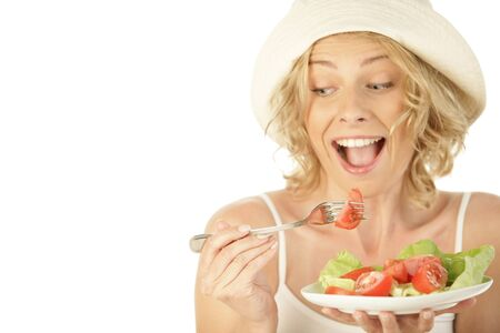Blonde woman eating vegetable salad isolated on white background photo