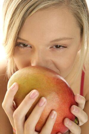 Young blonde beauty eating mango photo