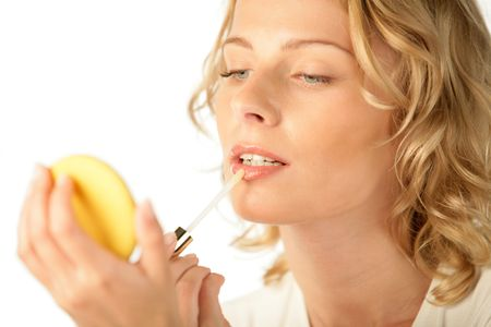 Portrait of young woman applying lip gloss photo