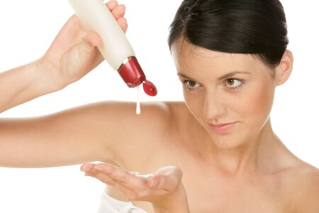 Young woman pouring lotion in hand isolated on white background photo