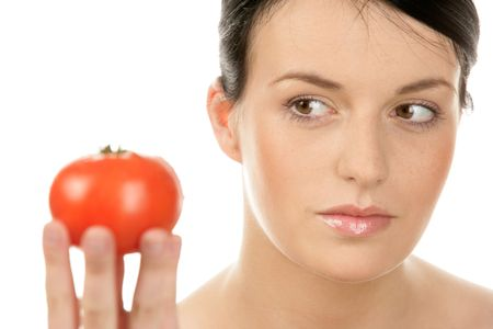 Portrait of young woman with tomato isolated on white background photo