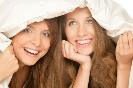 Two smiling teenage girls below duvet photo