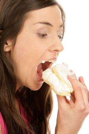 femme bouche ouverte: Portrait de jeune femme de manger le gâteau à la crème isolé sur fond blanc