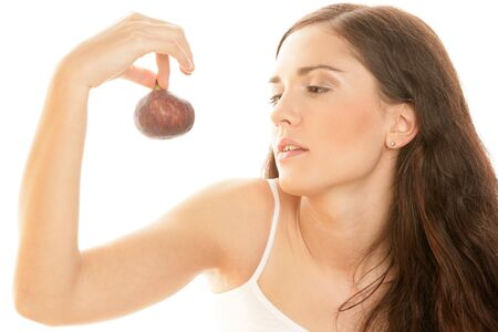 25 30 years old: Portrait of young woman holding fig isolated on white background