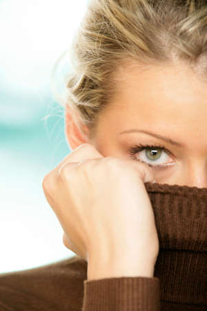 covering: Woman covering face with turtleneck looking at the camera