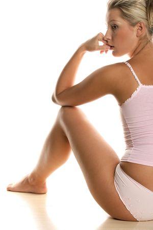 vrouw ondergoed: Jonge vrouw dragen roze underclothes zitten op de vloer