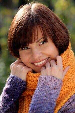Portrait of beautiful young woman wearing orange scarf photo