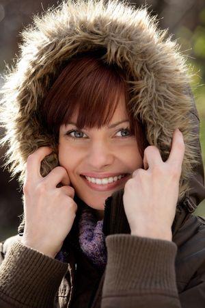Portrait of beautiful young woman wearing fur hood photo