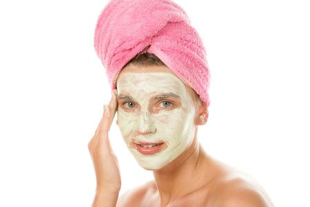 Woman applying facial cream and drying hair with towel photo