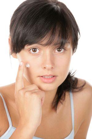 Teenage girl applying facial cream photo