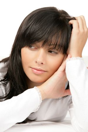 dark haired woman: Pensive teenage girl bedding Stock Photo