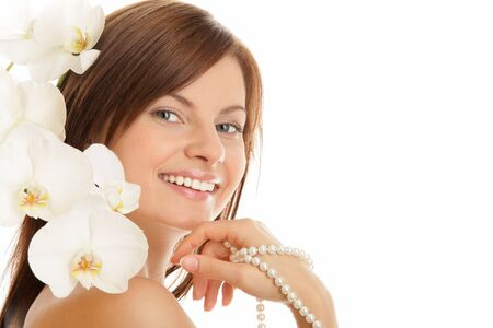 Portrait of young woman with pearl necklace and orchid photo