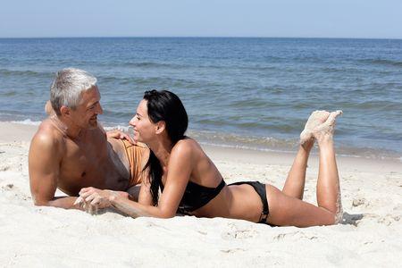 jeune vieux: Couple m�r attrayante relaxant sur la plage Banque d'images