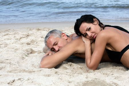 Attractive mature couple relaxing on the beach