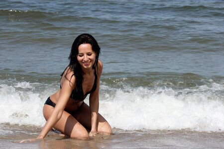 Attractive tanned woman on the beach photo