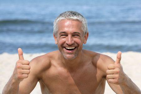 nackte brust: Handsome gl�cklich Mann, die Daumen aufzugeben, am Strand