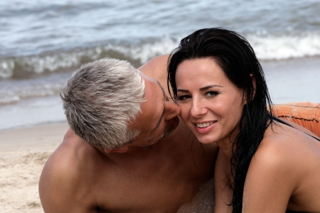 middle aged men: Attractive mature couple relaxing on the beach