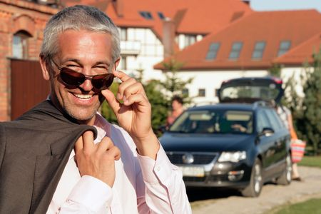 Handsome mature businessman standing before house and car Stock Photo