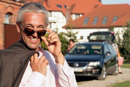 Handsome mature businessman standing before house and car Banco de Imagens