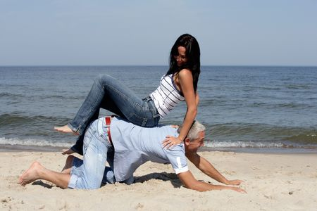 Happy middle aged couple having fun on the beach photo