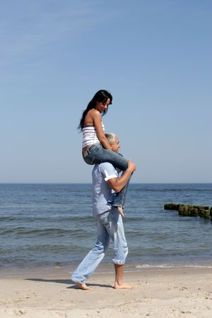Attractive woman riding on mans shoulders on the beach