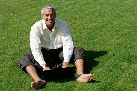 Barefoot businessman sitting on grass with laptop computer photo
