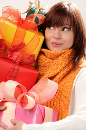Portrait of young surprised woman holding pile of gifts Banco de Imagens