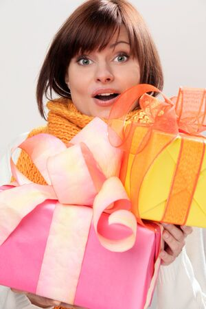 Portrait of young surprised woman holding pile of gifts photo