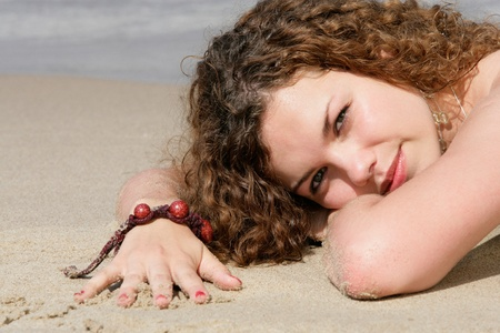 Teenage girl lying on sand on the beach Stock Photo - 12174689