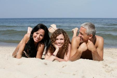 35 40 years: Happy family lying on sandy beach Stock Photo