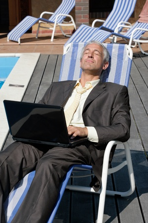 pool deck: Mature businessman relaxing next to the pool