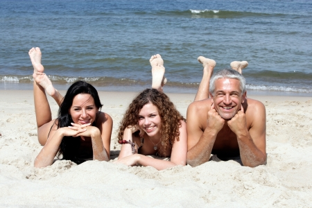 Family lying on sandy beach photo