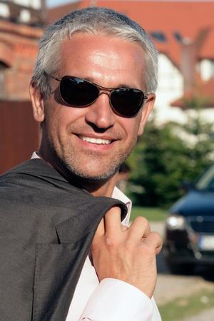 Attractive mature businessman standing in front of house Banco de Imagens