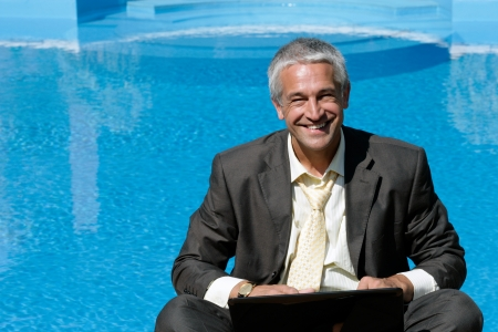 one senior adult man: Mature businessman working next to the pool