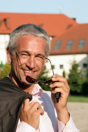 Handsome mature businessman standing in front of house Stock Photo